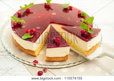 Cheesecake with jelly and cranberries on wooden background