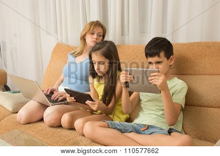 mother, daughter, son with laptop and tablet pc. Internet addiction.