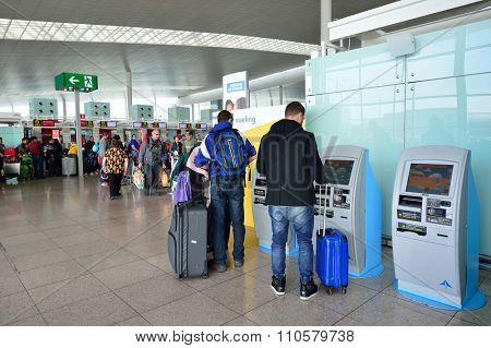 BARCELONA, SPAIN - NOVEMBER 20, 2015: passengers use check-in kiosks in Barcelona airport. Barcelona-El Prat Airport is an international airport. It is the main airport of Catalonia.