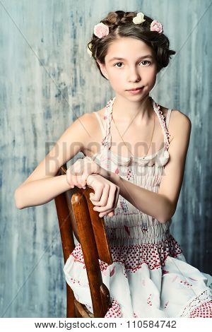 Vintage potrait of a beautiful girl with braided hair wearing summer sundress. Children fashion. Retro style.