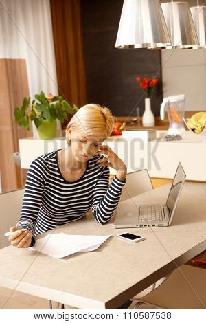 young blonde woman sitting at table, working at home.