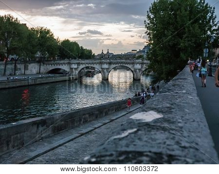 People Stroll By The Seine On A Summer Evening In Paris
