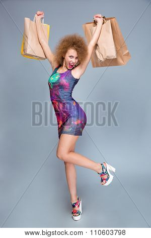 Joyful emotional pleased content attractive pretty young curly female in colorful dress and platform summer shoes excited after good shopping