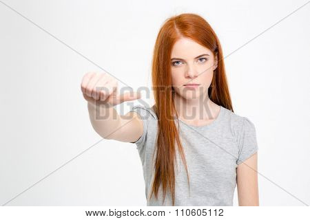Serious unhappy pretty woman with long red hair pointing away with thumb isolated over white background