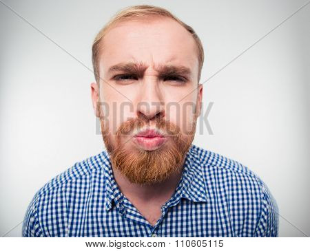 Portrait of a funny young man inflate his cheeks isolated on a white background
