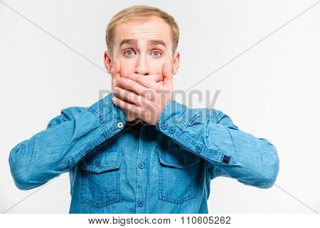 Shocked dazed young blond man closed his mouth by hands over white background