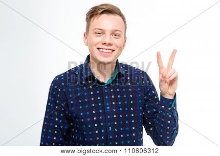 Happy handsome blond young man in checkered shirt showing victory sign with fingers over white background