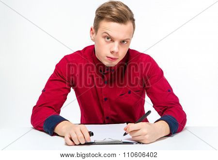 Suspicious curious attractive young male in red shirt with raised eyebrow writing on clipboard over white background
