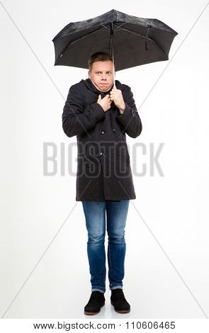 Amusing young man in black coat and jeans standing and feeling cold under umbrella over white background