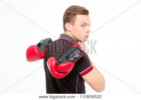 Annoyed sad blond young male carrying boxing gloves and looking back isolated over white background