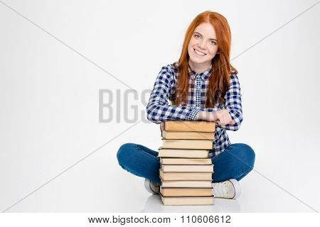 Cheerful joyful young lady with long red hair sitting with legs crossed and leaning on stack of books over white background