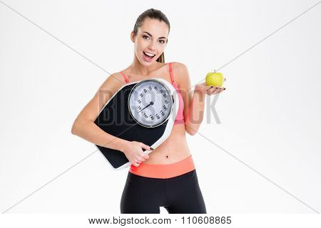 Excited positive fitness girl in tracksuit holding weighing scale and apple over white background