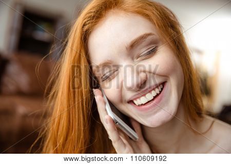 Closeup portrait of a smiling redhead woman with closed eyes talking on the phone