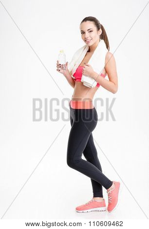Full length of cheerful attractive young fitness woman posing with white towel and bottle of water over white background