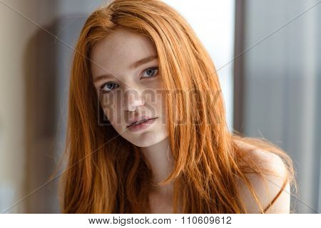 Portrait of a lovely redhead woman looking at camera