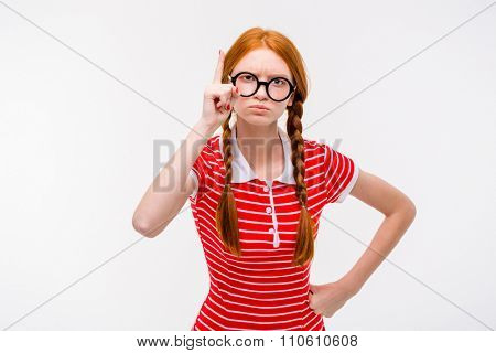 Strict young redhead woman with two braids in round glasses pointing up isolated on white background