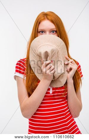 Embarrassed shy redhead young woman hiding her face behind hat posing on white background