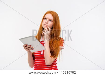 Pensive beautiful attractive concentrated young woman in red striped top  with long red hair thinking and holding tablet