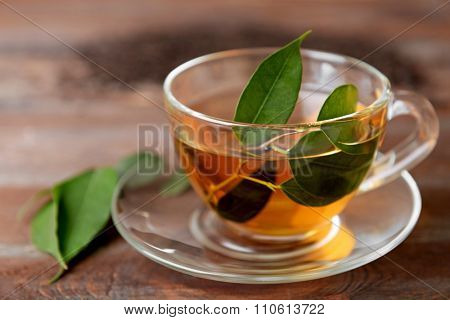 Glass cup of tea with green leaves on wooden background