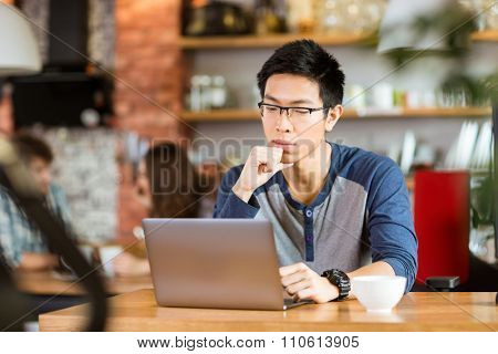 Concentrated pensive young handsome asian man in glasses sitting in cafe, thinking and using laptop