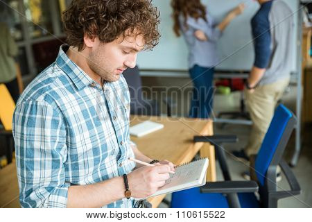 Thoughtful confident young curly man in blue plaid shirt making notes in notebook and creating project with colleagues