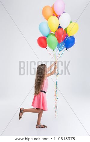 Side view portrait of little girl with colourful balloons isolated on a white background
