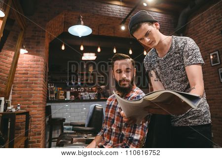 Young hairstylist and attractive bearded client looking through magazine sitting in barbershop
