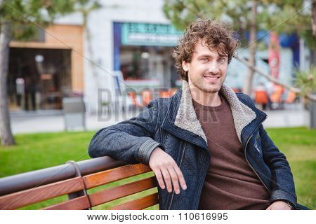 Cheerful happy joyful content curly young male in black jacket sitting and resting on the bench in the park