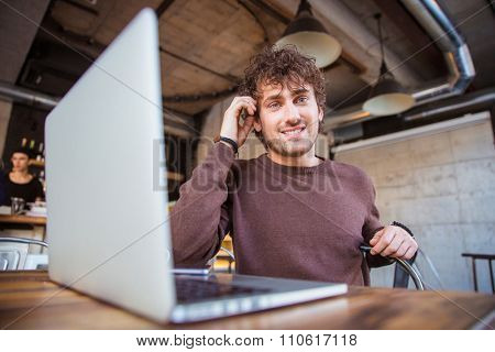 Young happy content attractive joyful smiling handsome man working using laptop