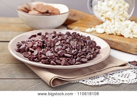Chocolate morsels on plate, on wooden background
