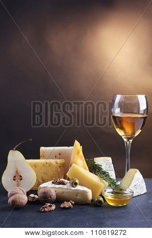 Different kinds of cheese, wine glass, pear, nuts and olives, on the table, close up