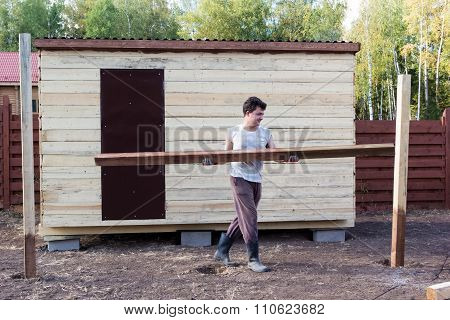 Man Carries Wooden Beam Near The Barn