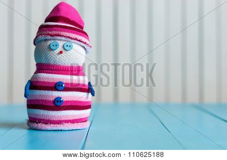 Funny little handmade snowman in a white and marsala stripy sweater on wooden background. Christmas