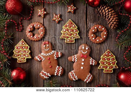 Gingerbread man and woman couple christmas cookies composition in xmas tree decorations frame