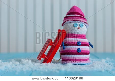 Handmade snowman in marsala color sweater with red sled on snow In winter. Christmas postcard backgr