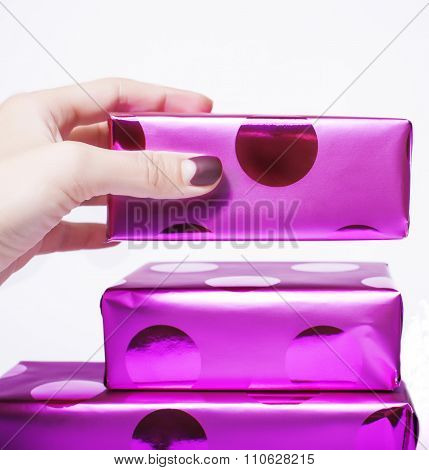 woman manicured hand puting christmas gift to rest pile of gifts close up isolated