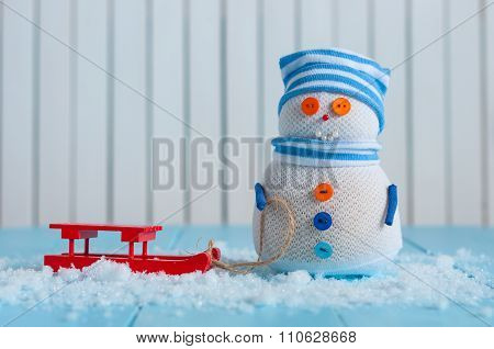 Handmade snowman in striped cap with red sled on snow In winter. Christmas postcard background, empt