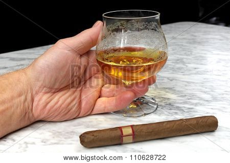 Hand Of A Man With A Cigar And A Glass Of Brandy On The Marble Table