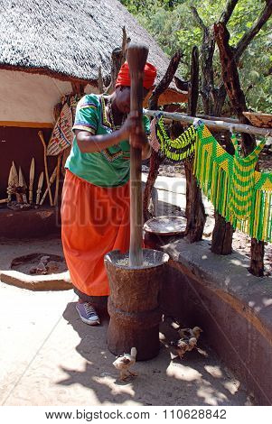 African Woman In Multicolor Dress Cooking Maize Meal At Cultural Village Lesedi, South Africa.