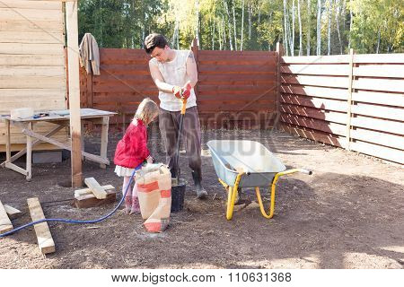 Girl Pours Water In A Bucket Of Cement Helping Dad