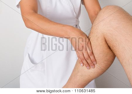 Female Physiotherapist Massaging The Leg Of Male Patient In A Physio Room.