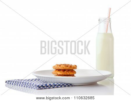 Stack of three homemade peanut butter cookies on white plate on blue napkin and bottle of milk