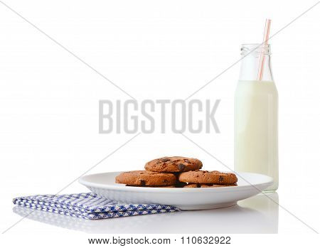 Pile of homemade chocolate chip cookies on white ceramic plate on blue napkin and bottle of milk