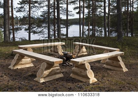 Outdoor rustic seats, long-seat for backpackers by a river.