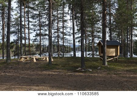 Outdoor rustic cabin and fireplace for backpackers by a river.