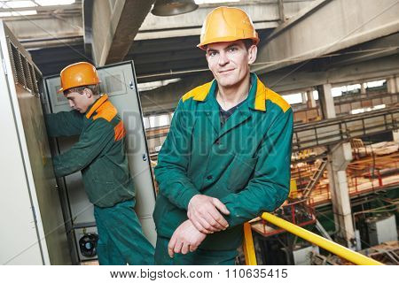 young adult electrician builder engineer in front of his co-worker screwing equipment in fuseboard