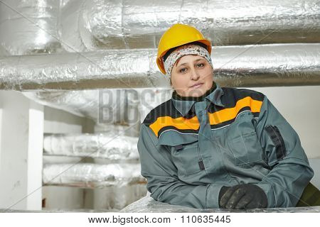 Thermal insulation. Female insulation worker in front of isolated by glass wool and foil industrial pipes