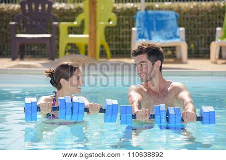 Man and woman holding floats in swimming pool