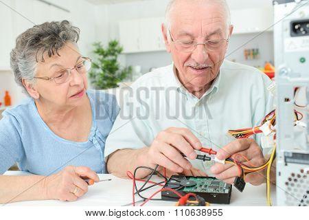 Elderly man checking computer with multimeter