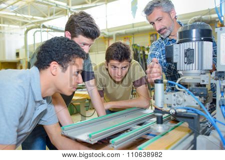 man operating a machine in front of his apprentices